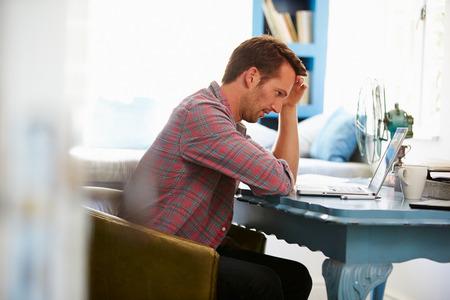 ノート パソコンとホーム オフィスの机で男を強調しました。