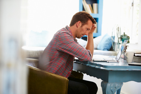 head home: Stressed Man At Desk In Home Office With Laptop