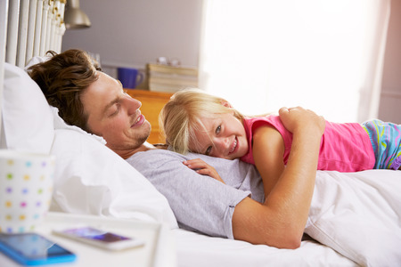 child in bed: Father And Daughter Lying In Bed Together