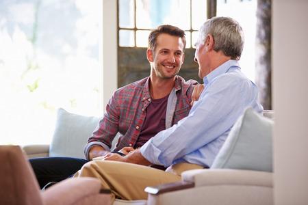 padres: Padre mayor con el hijo adulto se relaja en el sof� en el pa�s Foto de archivo