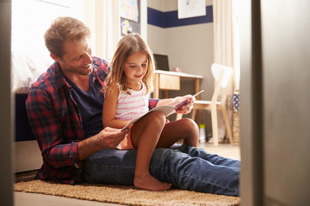 kids reading book: Father and young daughter reading together Stock Photo
