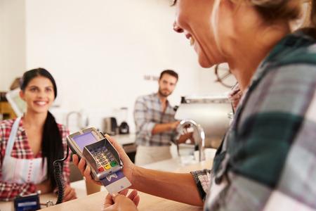 credit card: Mujer que paga con tarjeta de crédito en un café Foto de archivo