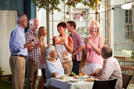 middle aged women: Group Of Friends Enjoying Outdoor Evening Drinks Party