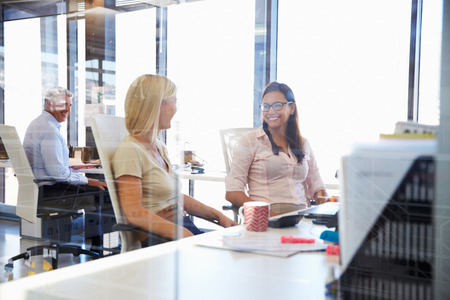work together: Happy colleagues talking in an office