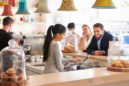 servings: People ordering at the counter in a cafe Stock Photo