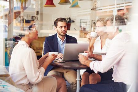 hombre tomando cafe: Reunión de negocios en un café