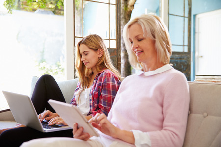 adult: Mature Mother With Adult Daughter Using Digital Devices