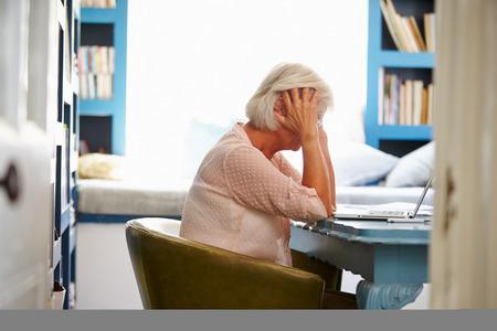 personas sentadas: Destac� Mujer Mayor En El Escritorio En Home Office con la computadora port�til Foto de archivo