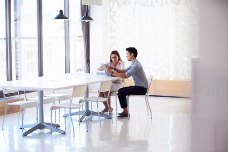 Twee mensen die werken met digitale tablet in lege zaal