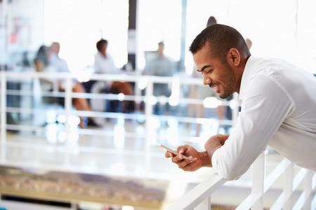 hombres jovenes: Retrato del hombre en la oficina con tel�fono, sonriendo