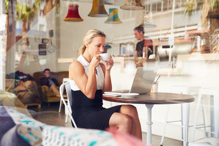 woman shop: Business woman sitting at a table in small coffee shop Stock Photo