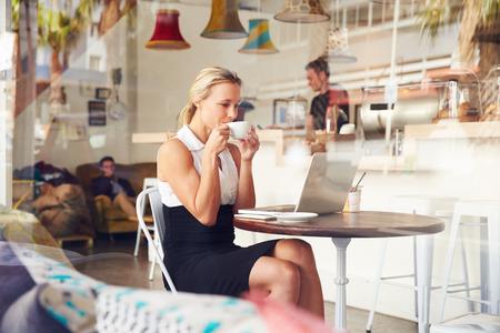 internet cafe: Mujer de negocios sentado en una mesa en la peque�a tienda de caf�