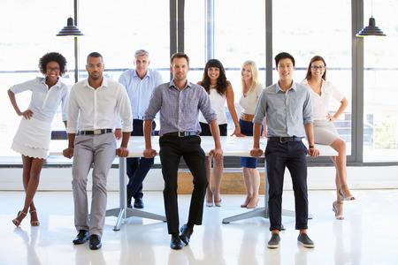 Coworkers posing to camera in meeting room Standard-Bild