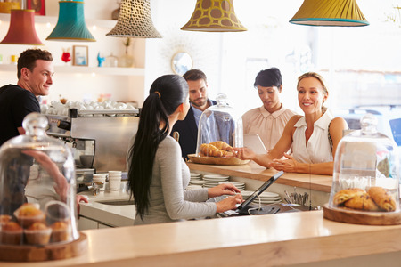 small group: Woman ordering at the counter in a cafe