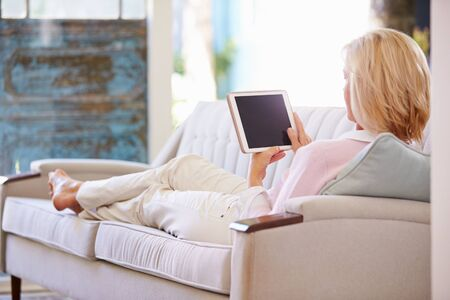 woman on couch: Mature Woman Relaxing On Sofa At Home Using Digital Tablet