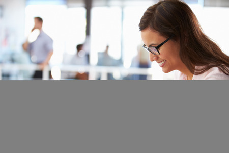 tecnologia: Ritratto di donna sorridente in ufficio con tavoletta, vista laterale Archivio Fotografico
