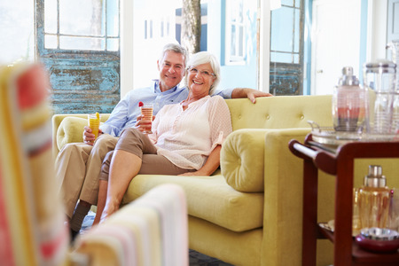 couple on couch: Senior Couple At Home Relaxing In Lounge With Cold Drinks Stock Photo