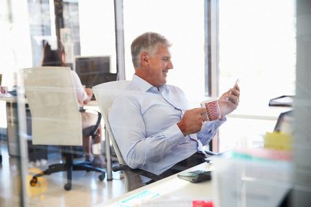 Man at work using smart phone, office interior Stock Photo