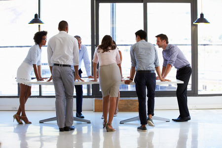 Colleagues standing around a conference table photo
