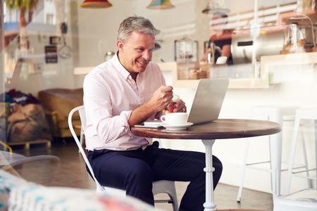 Mann mittleren Alters sitzt in einem Café