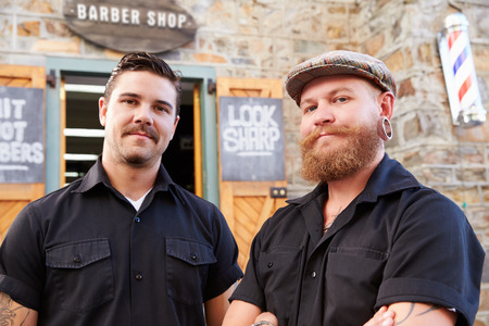 barber: Portrait Of Two Hipster Barbers Standing Outside Shop