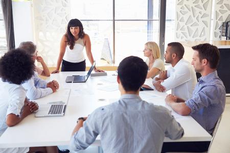 Femme d'affaires présente à ses collègues lors d'une réunion Banque d'images - 41393421