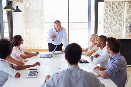 gerente: Hombre de negocios maduro que presenta a sus colegas en una reunión