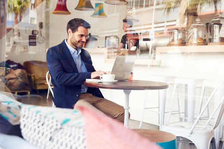 man side view: Young man using laptop at a cafe Stock Photo