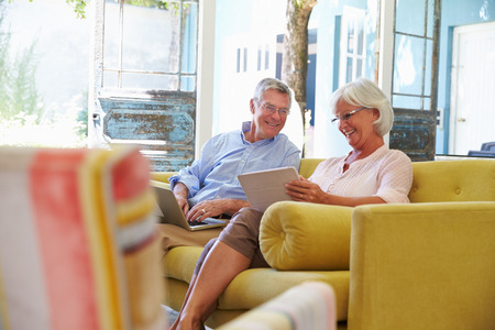 senior home: Senior Couple At Home In Lounge Using Digital Devices