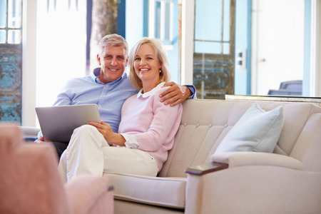 Mature Couple At Home In Lounge Using Laptop Computer