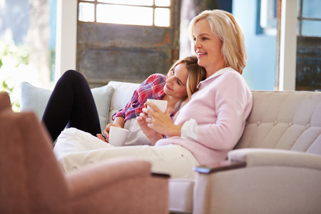 relaxing at home: Mature Mother With Adult Daughter Watching TV At Home Stock Photo
