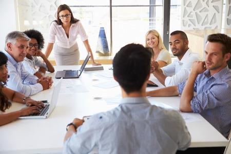 personas escuchando: Empresaria que presenta a sus colegas en una reunión Foto de archivo