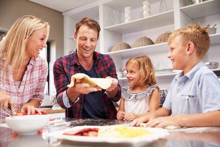happy family at home: Family making pizza together