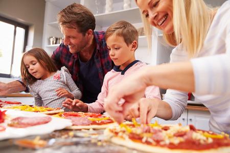 mujeres cocinando: Familia que hace la pizza juntos Foto de archivo