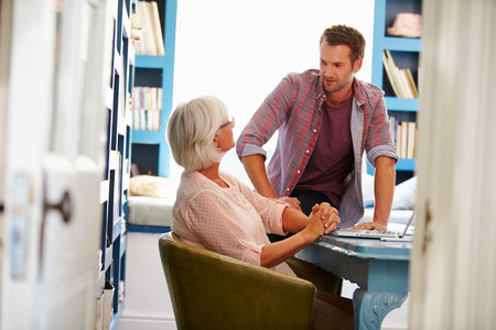 teaching adult: Son Giving Senior Parent Financial Advice In Home Office