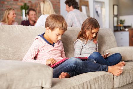 어른들이 즐기는 동안 신기술을 가지고 노는 아이들 스톡 콘텐츠