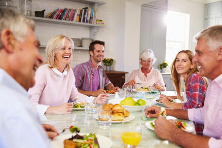 aged: Group Of Friends Enjoying Meal At Home Together