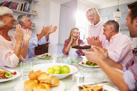 familia cenando: Madre Sirve torta de cumplea�os a la hija adulta Al comida familiar