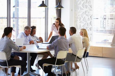 comunicação: De negócios que apresenta aos colegas em uma reunião