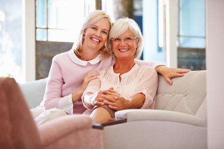 an adult person: Senior Mother With Adult Daughter Relaxing On Sofa Stock Photo