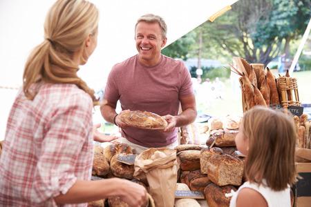 Family Het kopen van brood uit de bakkerij kraam op Farmers Market Stockfoto
