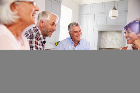 dinner party people: Group Of Mature Friends Enjoying Meal At Home Together Stock Photo
