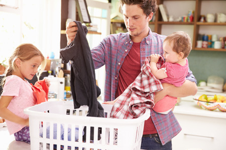 sorting: Father And Children Sorting Laundry In Kitchen