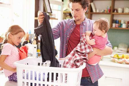 lavanderia: Padre y niños Ordenación de lavandería en la cocina Foto de archivo
