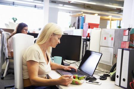 그녀의 책상에서 점심을 먹고 일하는 여성 스톡 콘텐츠