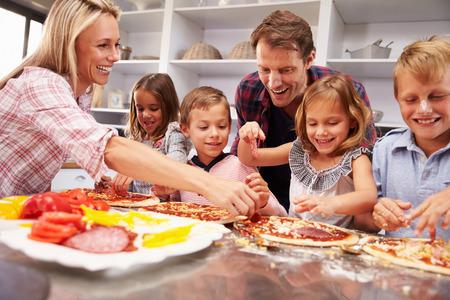 hombre cocinando: Familia que hace la pizza para la cena