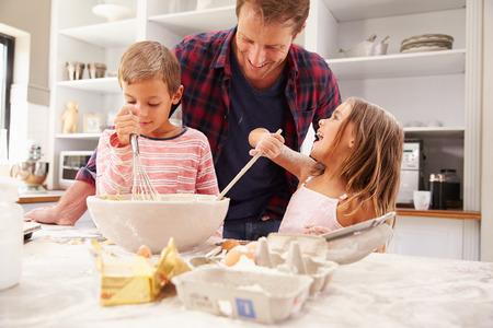 niños cocinando: Padre hornear con los niños Foto de archivo