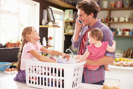 laundry: Padre que usa el teléfono móvil como Él ordena lavandería Con Niños Foto de archivo