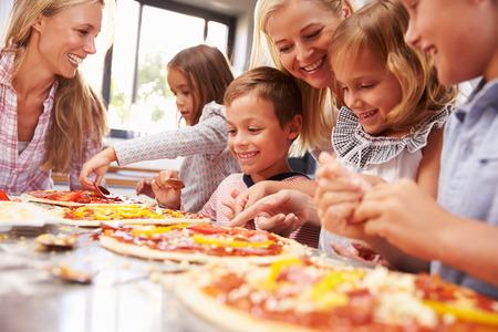 niños ayudando: Dos mujeres que hacen la pizza con los niños
