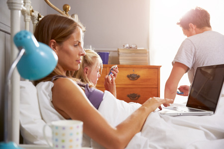 Family Lying In Bed Together Using Digital Devices photo